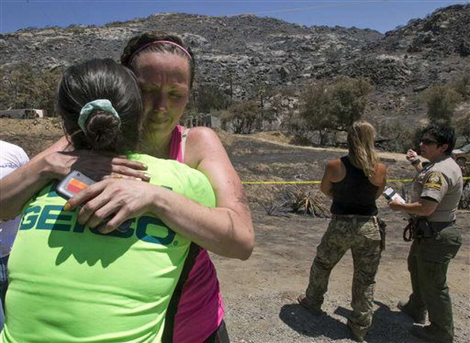 Neighbors Leann Mitsui, left, and Stephanie Riverburgh hugged after they and two other women discovered the burned remains of two victims of the Potrero, Calif., fire, Wednesday, June 29, 2016. San Diego County Sheriff's Department spokeswoman Jan Caldwell said the unidentified man and woman were found Wednesday near a boulder in Potrero, about 45 miles east of San Diego. The property had been under mandatory evacuation orders after a fire began on June 19 and has since spread to nearly 12 square miles. (John Gibbins/The San Diego Union-Tribune via AP) Photo: John Gibbins