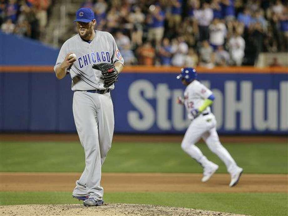 El cubano Yoenis Céspedes, de los Mets de Nueva York, al fondo, recorre las almohadillas luego de disparar un jonrón solitario al abridor de los Cachorros de Chicago, John Lackey, al frente, durante la sexta entrada del juego del jueves 30 de junio de 2016 en Nueva York. (AP Foto/Julie Jacobson) Photo: Julie Jacobson