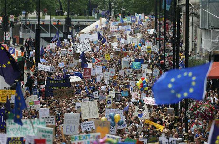 """""""Remain"""" supporters near Park Lane in London, before marching to Parliament Square to show their support for the European Union in the wake of the referendum decision for Britain to leave the EU, known as """"Brexit"""", Saturday July 2, 2016. Demonstrators wearing EU flags as capes and with homemade banners saying """"Bremain"""" and """"We Love EU"""" gathered on the streets around Park Lane for the March for Europe rally. (Daniel Leal-Olivas/PA via AP) Photo: Daniel Leal-Olivas"""