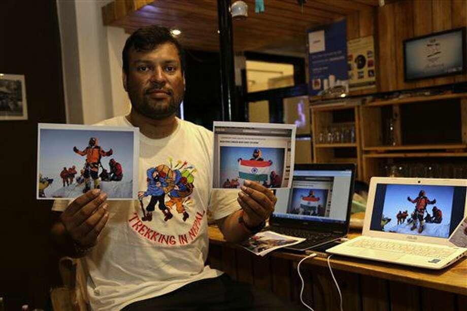 El alpinista Satyarup Sidhantha muestra en su mano derecha una fotografía donde sale él en la cima del monte Everest, y en la otra mano una foto que él asegura fue alterada por una pareja india para parecer que llegaron a la cumbre, el 4 de julio de 2016, en Calcuta, India. Las autoridades nepalíes investigan si los dos montañistas indios llegaron a la cima o alteraron fotografías. (AP Foto/ Bikas Das) Photo: Bikas Das