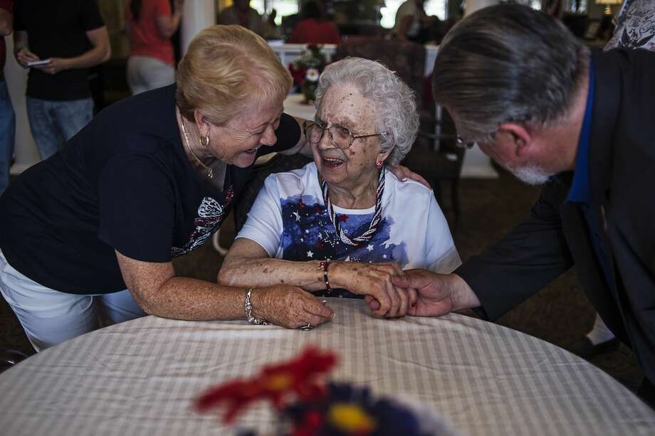 ERIN KIRKLAND | ekirkland@mdn.net Nottingham Place resident Ann Hanson, center, smiles while daughter-in-law Sue Hanson, left, and Midland city councilman and mayor pro tem Marty Wazbinski, right, wish her a happy birthday on Friday at Nottingham Place. Hanson will turn 100 on July 4th, so the living facility threw her a party. Photo: Erin Kirkland