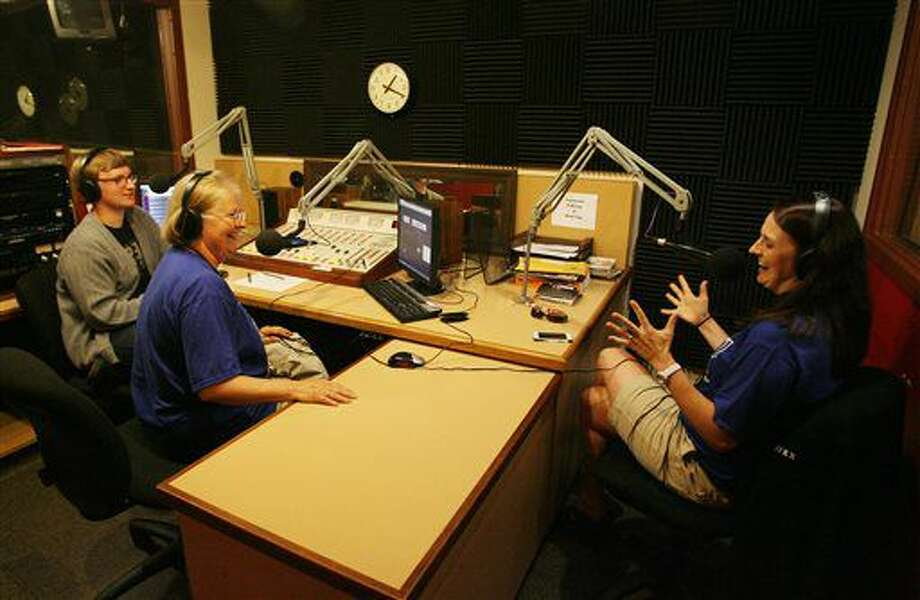 ADVANCE FOR USE SATURDAY, JULY 2 - In this photo taken June 25, 2016, Sharon Behl Brooks, center, associate professor of Journalism/Media Arts and English, speaks with Hastings College senior Sam Bennett and 2006 alumnus Meghan May on the air in the KFKX studio at the Gray Center for Communication Arts in Hastings, Neb., during a reunion and send off for the radio station. Amy Roh/The Hastings Tribune via AP) Photo: Amy Roh