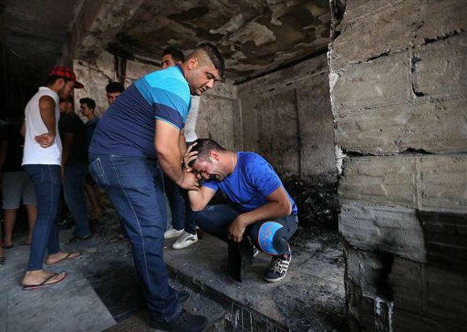Dos iraquíes se lamentan tras recorrer el sitio donde estalló un camión bomba en una zona comercial del barrio de Karada, en Bagdad, el lunes 4 de julio de 2016. (AP Foto/Hadi Mizban) Photo: Hadi Mizban