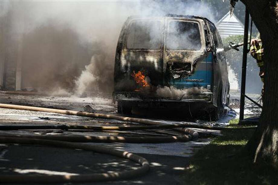 Firefighters douse a van that exploded and caught in the driveway of a home day care near Saginaw Township, Mich., Wednesday, June 29, 2016. Several children are safe after the van exploded and caused a fire that spread to a garage attached to the house, destroying books, supplies and toys. (Josie Norris/The Saginaw News via AP) Photo: Josie Norris