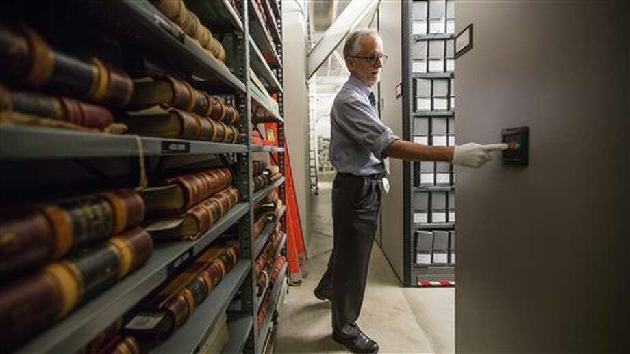 ADVANCE FOR WEEKEND EDITIONS, JULY 9-10 - In this photo taken June 16, 2016, City Archivist Scott Cline pushes a button to move a wall of files in City Hall in Seattle. Cline is retiring after 31 years, having built an organized archive of Seattle documents, photos and maps. (Steve Ringman/The Seattle Times via AP) Photo: Steve Ringman