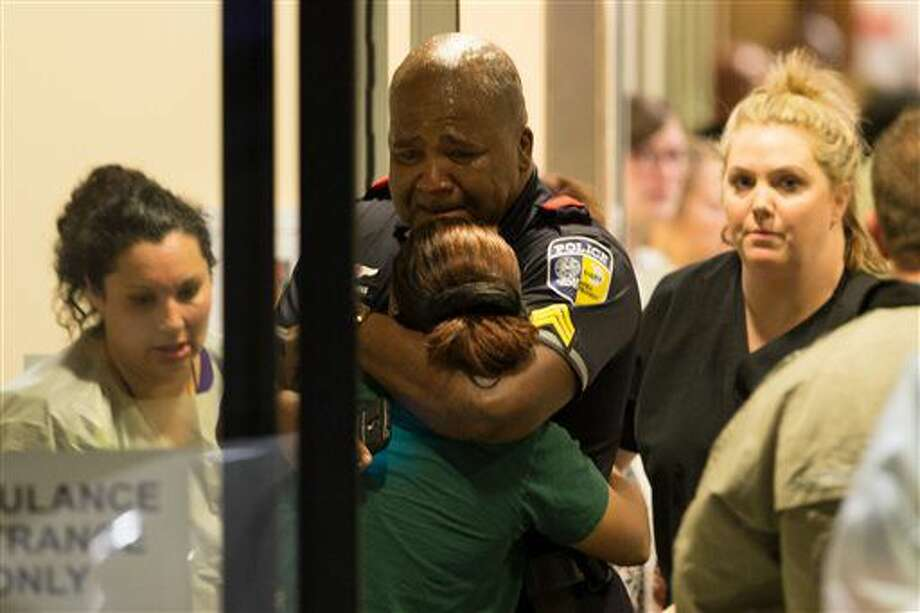 A Dallas Area Rapid Transit police officer receives comfort at the Baylor University Hospital emergency room entrance Thursday, July 7, 2016, in Dallas. Police say one rapid-transit officer has been killed and three injured when gunfire erupted during a protest in downtown Dallas over recent fatal shootings by police in Louisiana and Minnesota. (Ting Shen/The Dallas Morning News via AP) Photo: Ting Shen