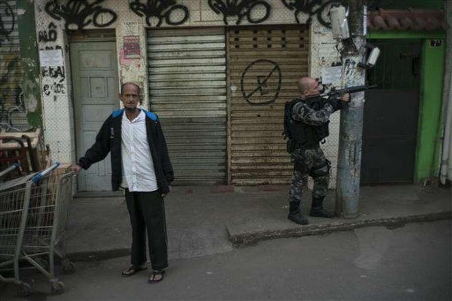 Un agente policial, parapetado detrás de un poste, apunta durante una operación contra traficantes de drogas en la favela de Jacarezinho, en Río de Janeiro, el miércoles 29 de junio de 2016 (AP Foto/Felipe Dana) Photo: Felipe Dana