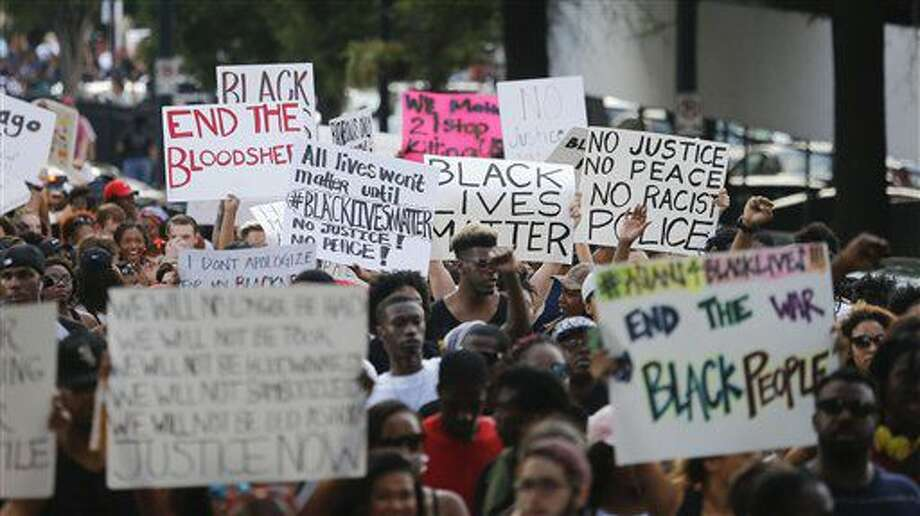 Demonstrators march through downtown Atlanta to protest the shootings of two black men by police officers, Friday, July 8, 2016. Thousands of people marched along the streets of downtown to protest the recent police shootings of African-Americans. Atlanta Police Chief George Turner and Atlanta Mayor Kasim Reed said earlier in the day that people have the right to protest this weekend but urged them to cooperate with law enforcement. (AP Photo/John Bazemore) Photo: John Bazemore