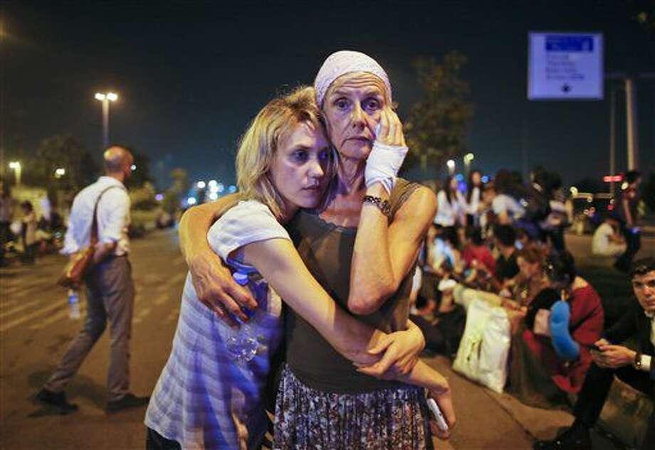 Dos pasajeras se abrazan mientras esperan ante el aeropuerto de Atartuk, en Estambul, en la madrugada del miércoles 29 de junio de 2016. (AP Foto/Emrah Gurel) NO PUBLICAR EN TURQUIA Photo: Emrah Gurel
