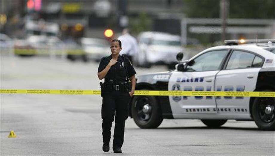 Un policía de Dallas resguarda la escena de un tiroteo mientras investigadores trabajan en el centro de Dallas, el viernes 8 de julio del 2016. La policía equipó a un robot con detonante de bombas para matar a un sospechoso armado tras un ataque armado a policías en Dallas, en lo que parece ser la primera vez que la policía estadounidense usa un robot para propósitos letales. Como tal, podría representar la última escalada en el uso de aparatos a control remoto y semiautónomos por parte de autoridades del orden. (Foto AP /LM Otero) Photo: LM Otero
