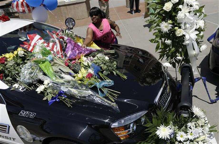 Cynthia Ware deposita flores en un monumento improvisado en las oficinas generales de la policía de Dallas el viernes 8 de julio de 2016, en Dallas, tras la muerte de cinco agentes por un francotirador. (AP Foto/Eric Gay) Photo: Eric Gay