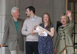 FILE - In this Monday, June 20, 2016 file photo, Chelsea Clinton holds her newborn son, Aidan, as she leaves Lenox Hill Hospital with her husband, Marc Mezvinsky, second left; father, former President Bill Clinton, left, and Democratic presidential candidate Hillary Clinton in New York. This is the couple's second child; their daughter's name is Charlotte. (AP Photo/William Regan)