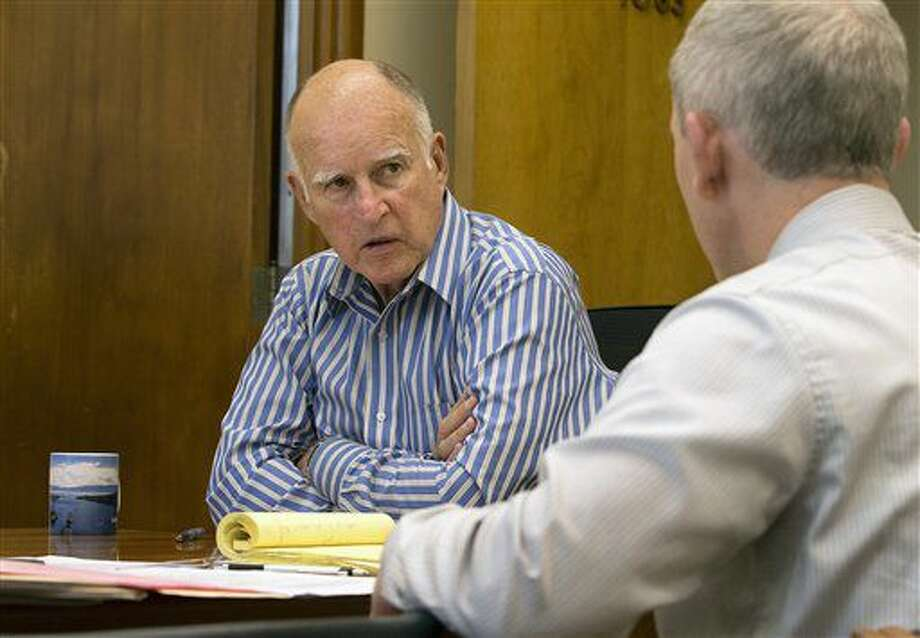 El gobernador de California, Jerry Brown, izquierda, discute una ley en consideración con Tom Dyer, secretario asistente para asuntos legislativos el jueves, 30 de junio del 2016. Brown firmó el viernes leyes de control de armas que requerirán que las personas deben entregar sus cargadores de alta capacidad y requerirán revisiones de antecedentes para todas las ventas de municiones, parte de los esfuerzos de los demócratas en el estado para fortalecer leyes de armas que ya están entre las más estrictas del país.(AP Foto/Rich Pedroncelli) Photo: Rich Pedroncelli