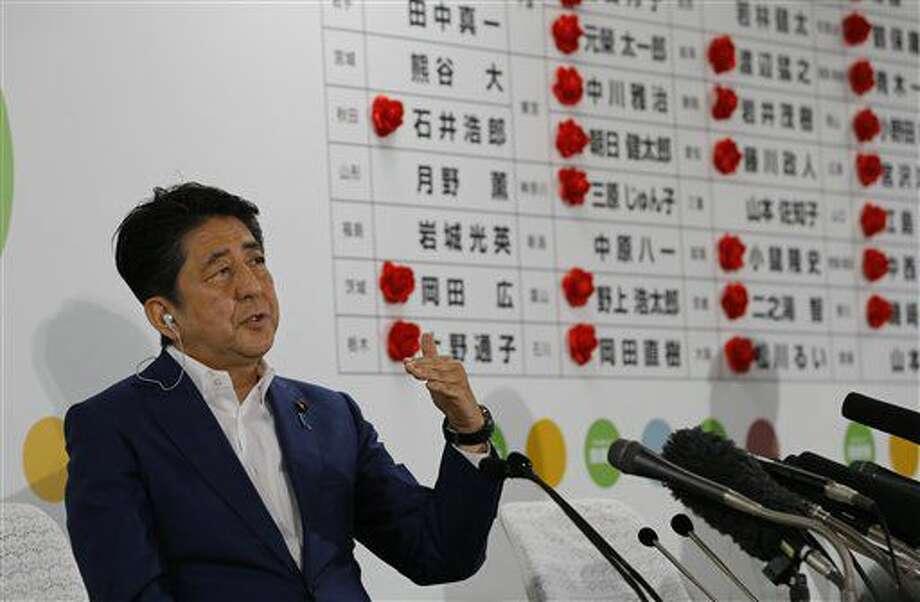 El primer ministro japonés Shinzo Abe responde la pregunta de un reportero durante una entrevista por televisión sobre el conteo de votos de la elección parlamentaria para la cámara alta, el domingo 10 de julio de 2016, en la sede de su partido, en Tokio. (AP Foto/Shizuo Kambayashi) Photo: Shizuo Kambayashi