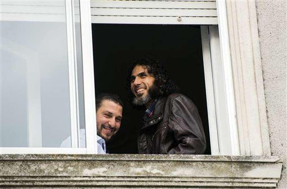 ARCHIVO - En esta fotografía de archivo del 5 de junio de 2015, el sirio Abu Wa'el Dhiab, derecha, y el tunecino Adel bin Muhammad El Ouerghi, ambos ex reos de la base estadounidense en Bahía de Guantánamo, sonríen junto a una ventana de la vivienda que compartían en Montevideo, Uruguay. Una aerolínea brasileña pidió a sus empleados que estén atentos respecto a Dhiab, pues aparentemente se desconoce su paradero. (AP Foto/Matilde Campodónico, archivo) Photo: Matilde Campodonico