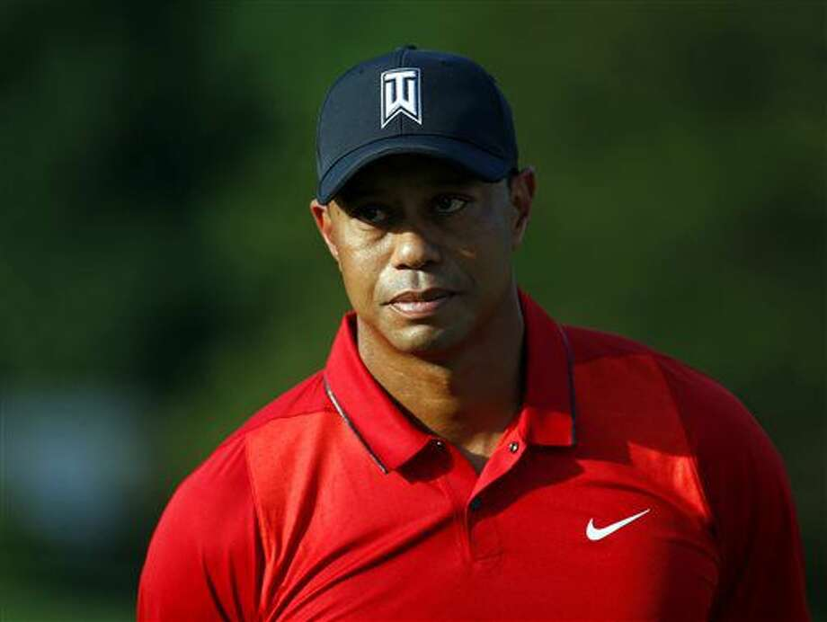 FILE - In this June 26, 2016, file photo, Tiger Woods stands on the 18th green during a trophy ceremony for Quicken Loans National PGA golf tournament winner Billy Hurley III in Bethesda, Md. Organizers say Friday, July 1, 2016, that Woods has withdrawn from the British Open at Royal Troon. (AP Photo/Patrick Semansky, File) Photo: Patrick Semansky