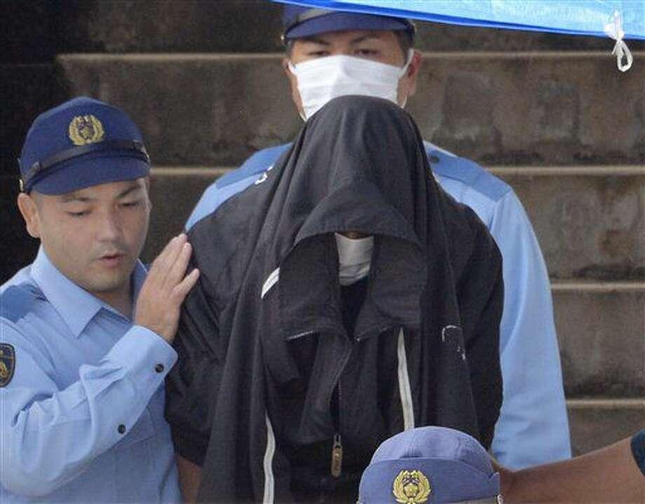 ARCHIVO - En esta imagen de archivo del 20 de mayo de 2016, agentes de policía escoltan a Kenneth Shinzato, en el centro, un estadounidense que trabajaba en una base de Estaados Unidos en Okinawa, ante la comisaría de Uruma, en la isla de Okinawa, sur de Japón, para entregarlo a la fiscalía como sospechoso de haber abandonado el cuerpo de una mujer desaparecida en abril de 2016. (Ryosuke Ozawa/Kyodo News via AP, Archivo) Photo: Ryosuke Ozawa