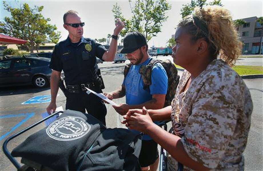 San Diego Homeless Outreach Team officer Brian Lucchesi canvasses several areas in the Midway and Sports Arena Blvd. area Wednesday, July 6, 2016, stopping to talk with people like Robert and Krista, two homeless people who stay in the area. The couple hadn't heard about the recent assaults on the homeless. On Wednesday, the San Diego Police Department's Homeless Outreach Team branched out to advise the area's homeless population about the increasing number of assaults on homeless individuals. So far two people have been murdered and two others badly beaten. (Peggy Peattie/San Diego Union-Tribune via AP) Photo: Peggy Peattie