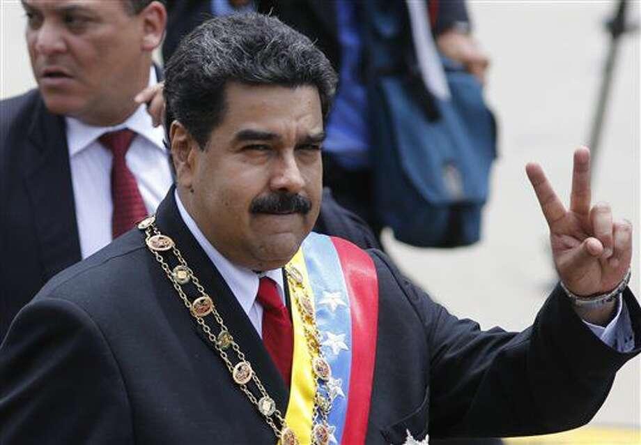 El presidente venezolano Nicolás Maduro hace la V de la victoria frente a sus partidarios durante un desfile por el Día de la Independencia en Caracas, Venezuela, el martes 5 de julio de 2016. Maduro ratificó el jueves 7 de julio de 2016 en sus cargos al ministro de Defensa, general en jefe Vladimir Padrino López, junto a los jefes de las comandancias del ejército y la aviación, y cambió al comandante general de la Guardia Nacional, que el año pasado estuvo en el centro de una polémica al ser señalado en Estados Unidos de que se estaría preparando una acusación en su contra por supuesta complicidad con traficantes de cocaína. (AP Foto/Ariana Cubillos) Photo: Ariana Cubillos