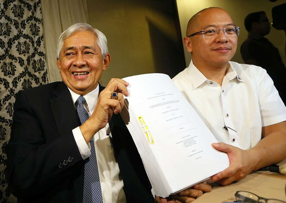 Associate Justice of the Supreme Court Francis Jardeleza (left) and former Solicitor General Florin Hilbay hold a photocopy of the U.N. international arbitration tribunal ruling favoring the Philippines. Photo: Bullit Marquez, Associated Press
