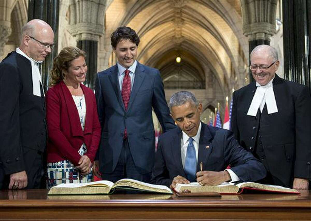 U.S. President Barack Obama signs the guest book during a welcome ceremony after arriving on Parliament Hill in Ottawa, as Canada's Speaker of the House of Commons Geoff Regan, Prime Minister Justin Trudeau and his wife Sophie Gregoire Trudeau and Speaker of the Senate George Furey (right) look on, Wednesday, June 29, 2016. (Justin Tang/The Canadian Press via AP)