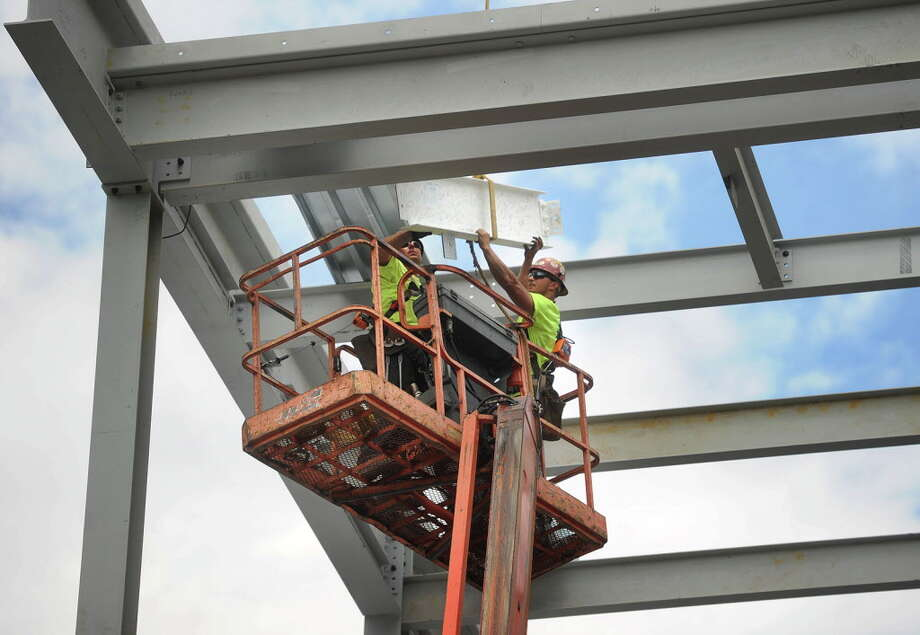 The final beam, painted white and signed by members of the Housatonic Community College community, is lowered into place during continued construction on the school's expansion project facing Lafayette Boulevard in Bridgeport, Conn. on Thursday, June 23, 2016. The additions to the school are scheduled to open for use in 2017. Photo: Brian A. Pounds / Hearst Connecticut Media / Connecticut Post
