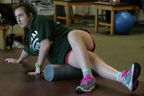 Former Reagan High School soccer player Lauren Jackson uses a foam roller as a part of her physical therapy at Momentum Physical Therapy & Sports Rehab. Jackson is recovering from a torn anterior cruciate ligament (ACL).