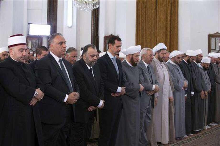 El presidente sirio Bashar Asad, en la fila delantera, cuarto desde la izquierda, reza en el primer día de Eid al-Fitr, el día que marca el fin de la festividad musulmana de Ramadán, en la Mezquita Safa, en Homs, Siria, el 6 de julio del 2016. Foto subida a la cuenta oficial de Facebook de la presidencia siria. (Presidencia de Siria via Facebook) Photo: Uncredited
