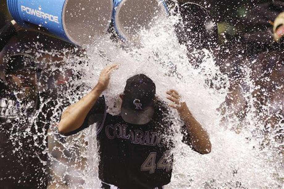 Compañeros del abridor de los Rockies de Colorado Tyler Anderson le lanzan agua tras el partido de la MLB contra los Filis de Filadelfia, el 9 de julio de 2016, en Denver. Anderson logró la primera victoria de su carrera en las mayores. (AP Foto/David Zalubowski) Photo: David Zalubowski