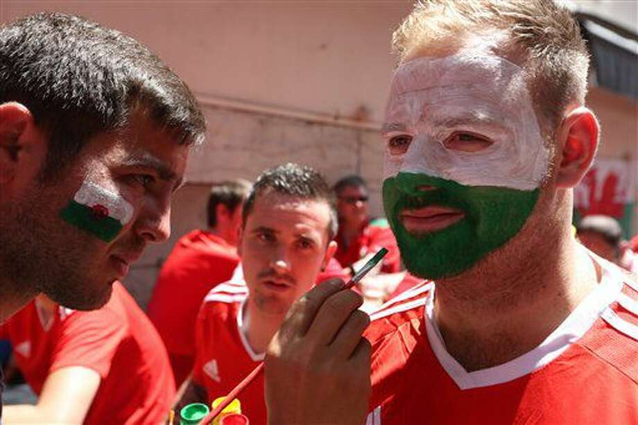 A man paints the flag of Wales on the face of a fan in central Lyon, France, Wednesday, July 6, 2016, prior the Euro 2016 semifinal soccer match between Portugal and Wales. (AP Photo/Thanassis Stavrakis) Photo: Thanassis Stavrakis