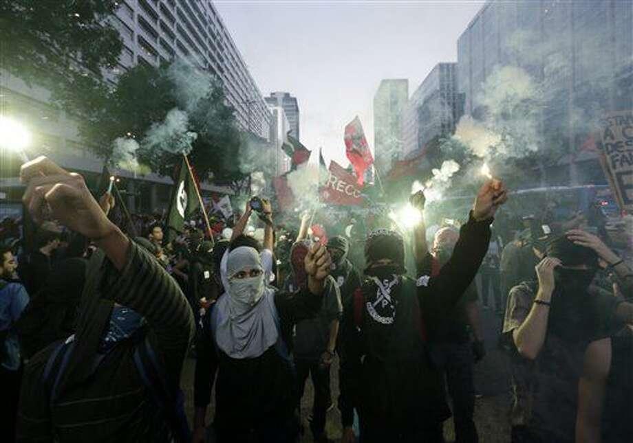 Estudiantes enmascarados encienden bengalas durante una marcha para exigir mejoras en la educación y protestar por el dinero gastado en los Juegos Olímpicos en Río de Janeiro, Brasil, 6 de julio de 2016. (AP Foto/Silvia Izquierdo) Photo: Silvia Izquierdo