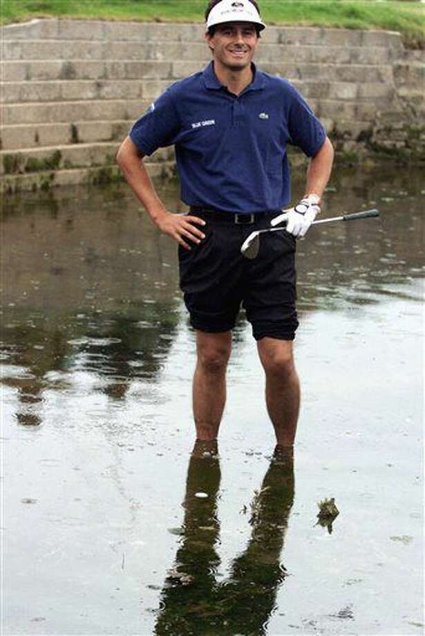 FILE - In this July 18, 1999, file photo, France's Jean Van de Velde smiles as he stands in the water of the Barry Burn that crosses the 18th fairway to see if his ball, bottom center, was playable during the final round of the 128th British Open Golf Championship at Carnoustie, Scotland. It's been five years since Jean Van de Velde retired from professional golf. Now, two months after turning 50, he figures it's time for a comeback. That will come this weekend at the Dick's Sporting Goods Open on the PGA's senior circuit. (AP Photo/File) Photo: Anonymous