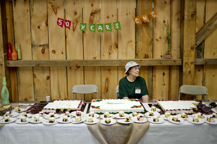 NICK KING | nking@mdn.net Volunteer Marijean Fitzgerald man the table where free cake was being given out during the 50th Anniversary Celebration on Saturday at the Chippewa Nature Center. Photo: Nick King/Midland Daily News