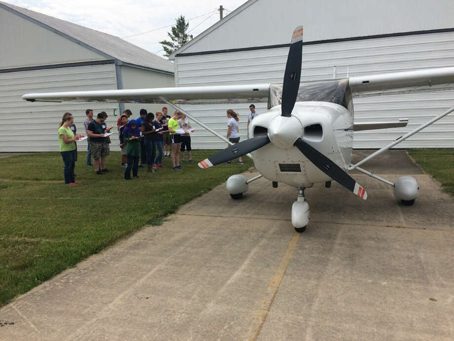 Students from the 21st annual Midland Aviation Camp check out an airplane at the Jack Barstow Municipal Airport. Campers experienced a variety of aviation-related activities, including lessons on weather, aerodynamics, history, GPS navigation and riveting. Photo: Photo Provided