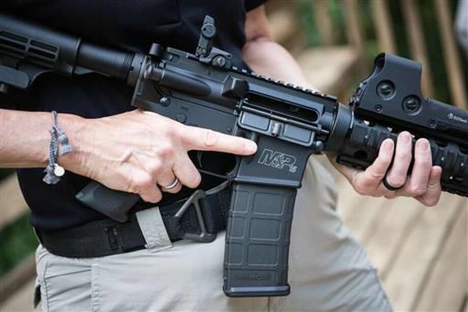 A Smith & Wesson M&P15 is held in Auburn, Georgia. An estimated 8 million AR-style guns have been sold since they were first introduced to the public in the 1960s, and about half of them are owned by current or former members of the military or law enforcement, according to the National Shooting Sports Foundation, which represents gunmakers. (AP Photo/Lisa Marie Pane)