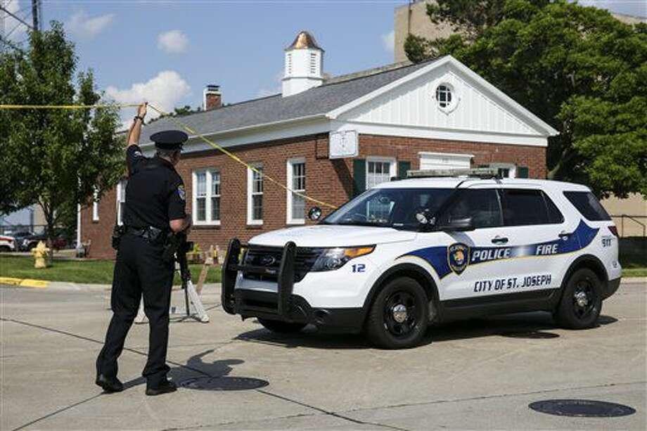 Un agente permite el paso de un vehículo policial afuera del tribunal del condado Berrien en St. Joseph, Michigan, el lunes 11 de julio de 2016. Dos agentes de la corte fueron muertos a tiros por un preso que arrebató el arma a un policía en su intento por escapar del lugar. El hombre fue abatido por otros policías, dijeron las autoridades. (Chelsea Purgahn/Kalamazoo Gazette vía AP) Photo: MBI -end-
