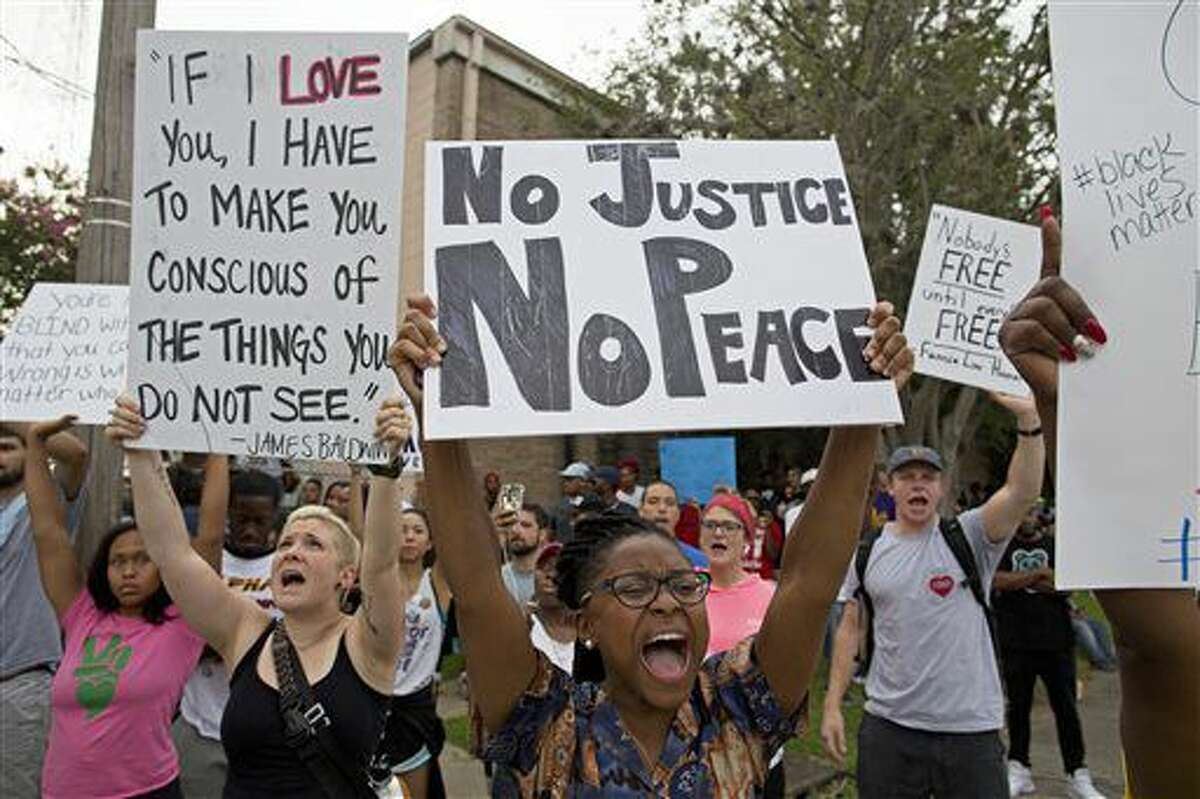 Police and protesters demonstrate in a residential neighborhood in Baton Rouge, La. on Sunday, July 10, 2016. After an organized protest in downtown Baton Rouge protesters wondered into residential neighborhoods and toward a major highway that caused the police to respond by arresting protesters that refused to disperse. (AP Photo/Max Becherer)