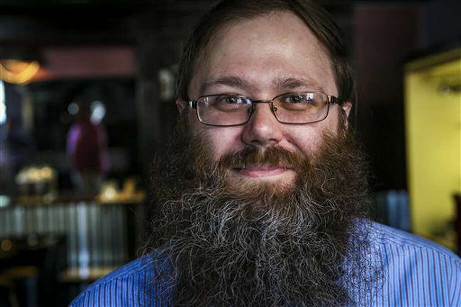 Journal Star Political Reporter Chris Kaergard poses for a photo before having his beard trimmed at Menzoil Men's Grooming Station & Barbershop in East Peoria, Ill., Saturday, July 9, 2016. Satisfied by the stopgap budget reached through compromise and bipartisanship in the capital, Kaergard decided to draw an end to the budget beard after 13 months and nearly 10 inches of facial hair. Guests were invited to help trim the beard down for a donation supporting organizations affected by the lack of a budget. (Andy Abeyta/Journal Star via AP) Photo: Andy Abeyta