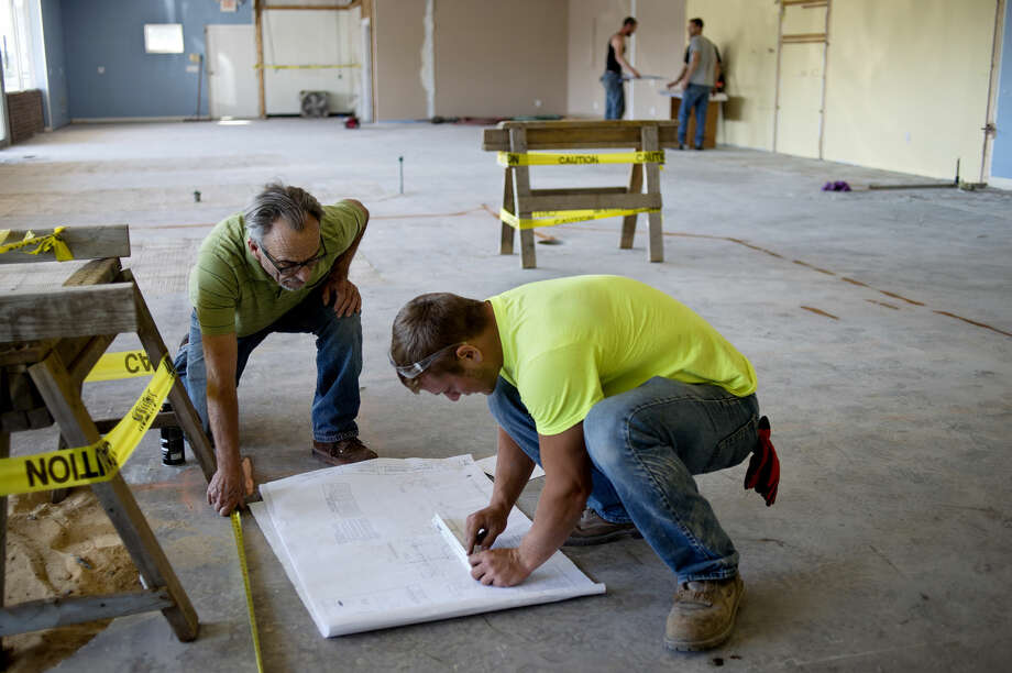 Tim Katz, left, and Noah Camilleri look over construction documents while mapping out the plumbing for the new location of Basil Tai Bistro at 459 E. Ellsworth in Midland. Construction is expected to be completed by late September. Photo: Brittney Lohmiller | Midland Daily News