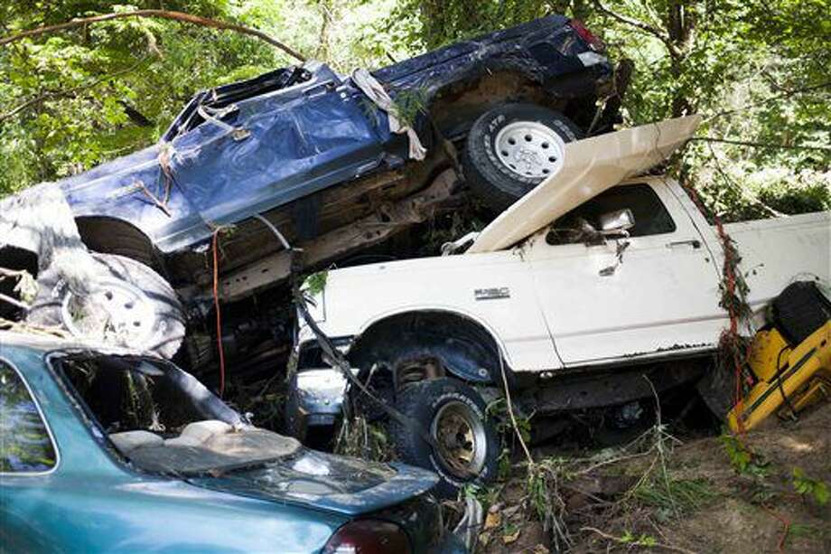 A pile of pickup trucks and other automobiles sit embedded in the sand and mud of a salvage yard in Rupert, W.Va., Sunday, June 26, 2016. (Christian Tyler Randolph/Charleston Gazette-Mail via AP) MANDATORY CREDIT Photo: Christian Tyler Randolph