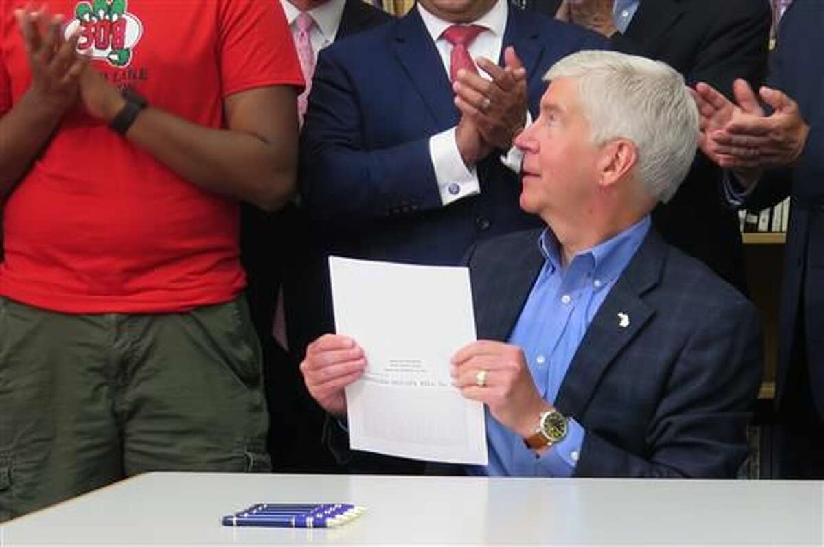 Gov. Rick Snyder is applauded by lawmakers and students as he signs a $16.1 billion education budget bill, Monday, June 27, 2016, at the James R. Geisler Middle School in Commerce Township, Mich. (AP Photo/David Eggert)