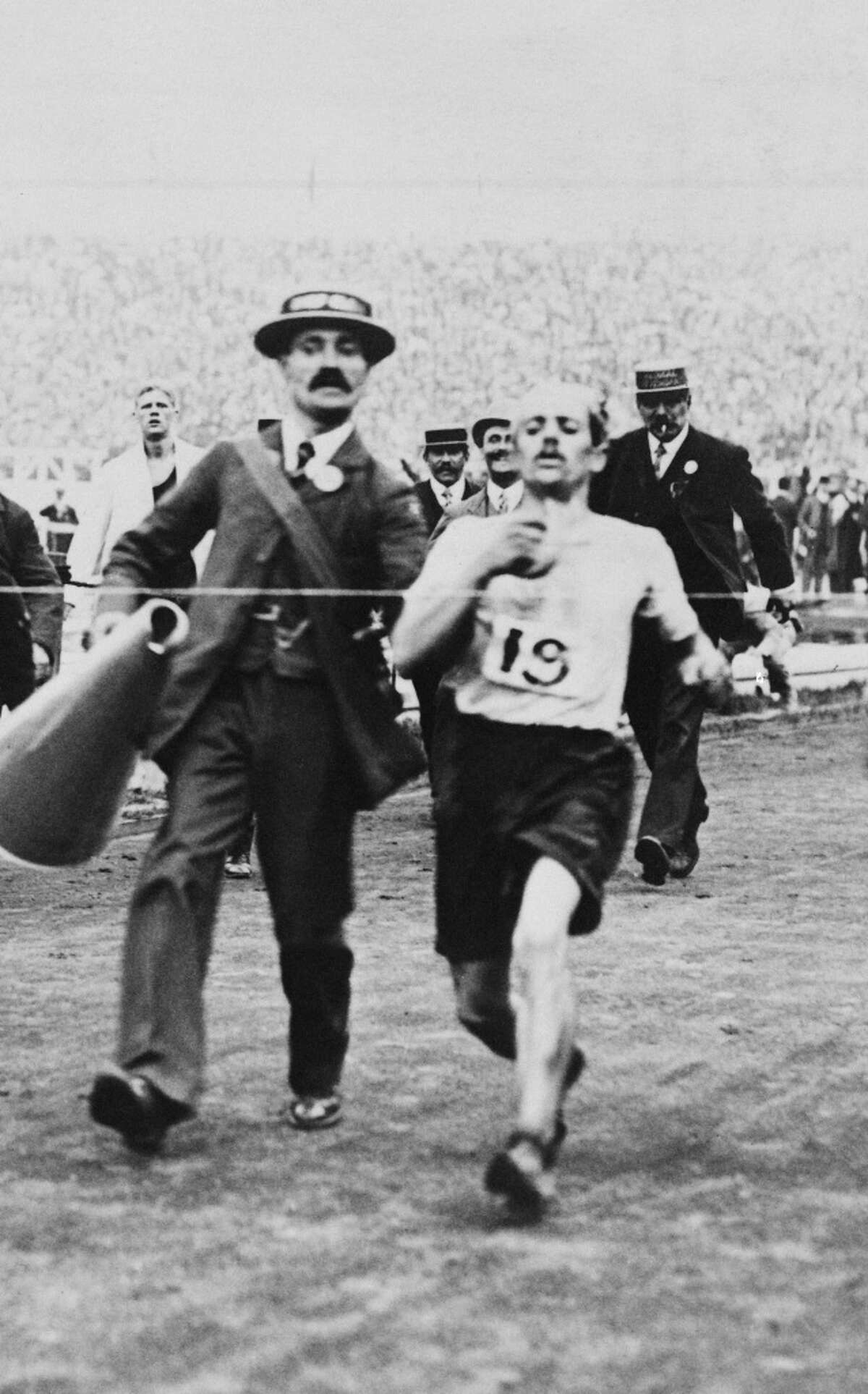 Dorando Pietri (1885-1942) of Italy, on the verge of collapse, is helped across the finish line in the Marathon event of the Olympic Games in London, July 24, 1908. He was subsequently disqualified and the title was given to John Hayes of the USA.