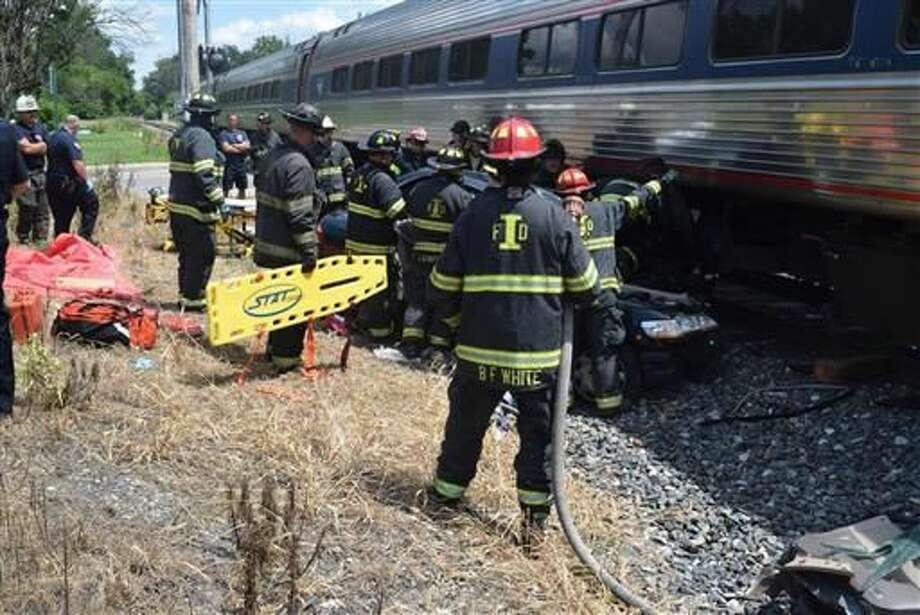 Emergency officials respond after a train and car crashed in Indianapolis on Saturday. The Indianapolis Fire Department says an Amtrak train slammed into a car at a crossing, injuring a woman and 3-year-old child who were in the vehicle. Photo: Rita L. Reith | Indianapolis Fire Department Via AP
