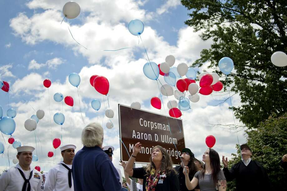 Debi Ullom, center, looks on as balloons are released during a dedication for the bridge named in honor of her son, U.S. Navy Corpsman Aaron Ullom, on Saturday at the Midland Armory. Ullom was killed in action on July 12, 2011, while serving in Helmond Province, Afghanistan. Photo: NICK KING | Nking@mdn.net