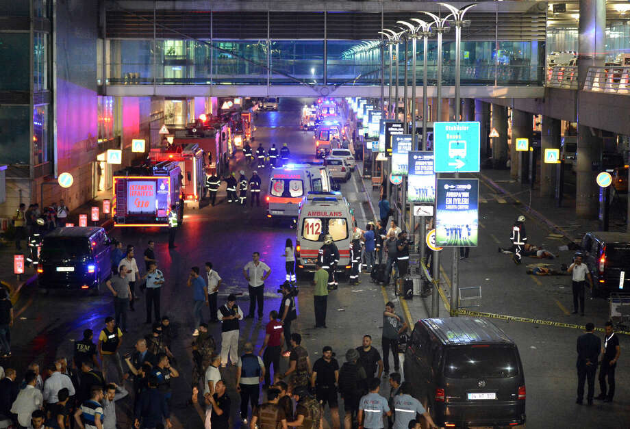Medics and security members work at the entrance of the Ataturk Airport after explosions in Istanbul, Tuesday, June 28, 2016. Two explosions have rocked Istanbul's Ataturk airport, killing several people and wounding others, Turkey's justice minister and another official said Tuesday. A Turkish official says two attackers have blown themselves up at the airport after police fire at them. The official said the attackers detonated the explosives at the entrance of the international terminal before entering the x-ray security check. (IHA via AP) TURKEY OUT Photo: SUB
