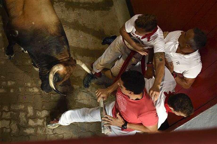Corredores perseguidos por un toro bravo de la ganadería de Cebada Gago a su entrada a la plaza de toros, en el segundo encierro de las Fiestas de San Fermín en Pamplona, en el norte de España, el viernes 8 de julio de 2016. (AP Foto/Alvaro Barrientos) Photo: Alvaro Barrientos