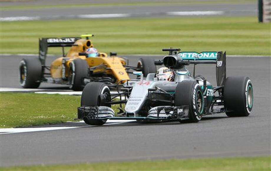 Mercedes driver Lewis Hamilton and Renault driver Jolyon Palmer, both of Britain, steer their cars during the first free practice session at the Silverstone race track, Silverstone, England, on Friday, July 8, 2016. The British Formula One Grand Prix will be held on Sunday July 10. (AP Photo/Luca Bruno) Photo: Luca Bruno