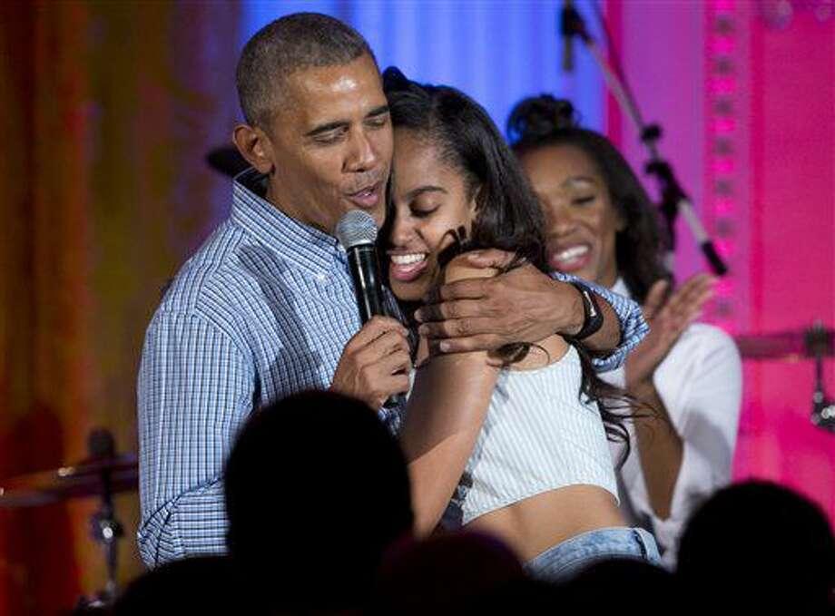 """El presidente Barack Obama abraza y le canta """"Happy Birthday"""" a su hija Malia Obama en el escenario durante un festejo por el Día de la Independencia en el Salón Este de la Casa Blanca, en Washington, el lunes 4 de julio de 2016, para miembros de las fuerzas armadas y sus familias. (AP Foto/Carolyn Kaster) Photo: Carolyn Kaster"""