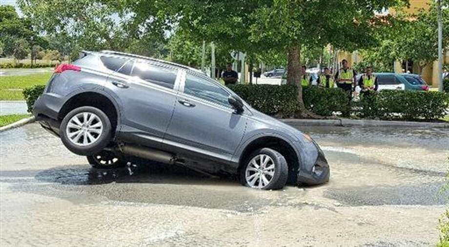 This photo provided by Mike Jachles Broward Sheriff Fire Rescue shows a vehicle partially swallowed by a 10-foot-by-10-foot sinkhole on Thursday, July 7, 2016 in Cooper City, Fla. Dolores Otero drove toward the drive-thru and her car went nose-first into the water. One of the car's back tires was left hanging in the air. Otero and her grandson got safely out of the vehicle, which began to fill with water. (Mike Jachles/Broward Sheriff Fire Rescue via AP) Photo: Mike Jachles