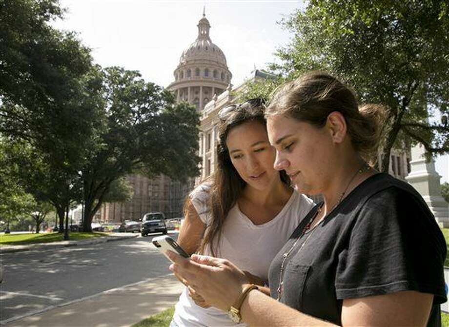 Tina Bizaca, left, and Sarah Boutwell play the augmented-reality smartphone game Pokémon Go at the Capitol in Austin, Texas, Monday July 11, 2016. (Jay Janner/Austin American-Statesman via AP) Photo: Jay Janner